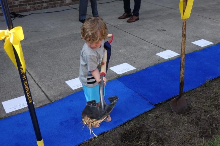 child shoveling at VLHS ground breaking
